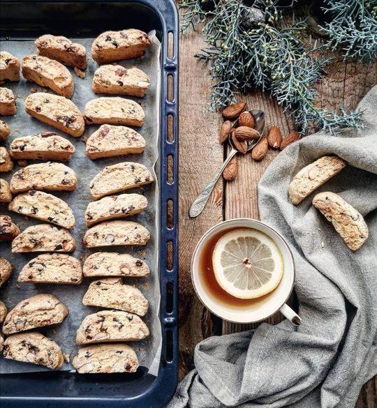 una teglia di biscotti visti dall'alto, con una tazza di the con limone e un cucchiaino con mandorle