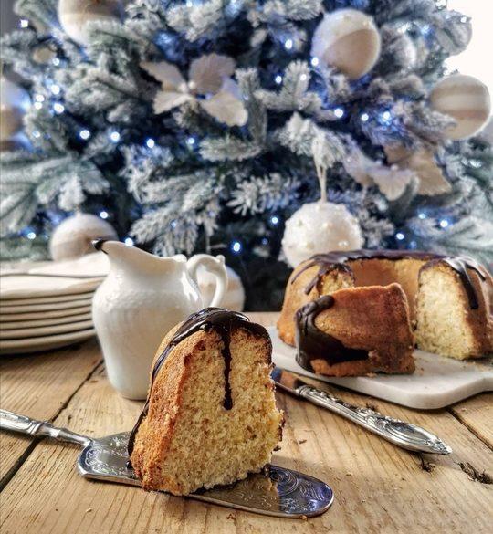una ciambella tagliata, con colata di cioccolato, sullo sfondo dei piatti e un albero di Natale