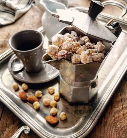 un vassoio con una tazzina e una moka colma di nocciole pralinate