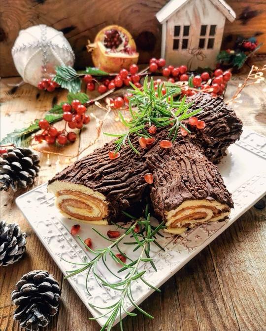 un tronchetto di Natale dolce al cioccolato posato su un tavolo di legno, servito in un piatto rettangolare bianco. sullo sfondo una melagrana e una palla di Natale