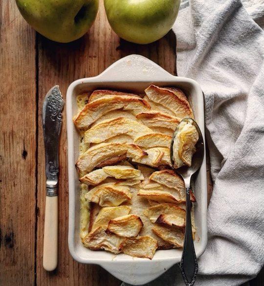 visione dall'alto di una pirofila con mele a fettine, straccio di lato e dall'altro lato un coltello, in alto della foto 2 mele