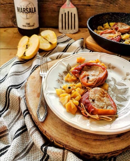 un piatto con della carne e mele cotte, a lato una forchetta e un canovaccio, sullo sfondo una mela tagliata, la padella e una bottiglia