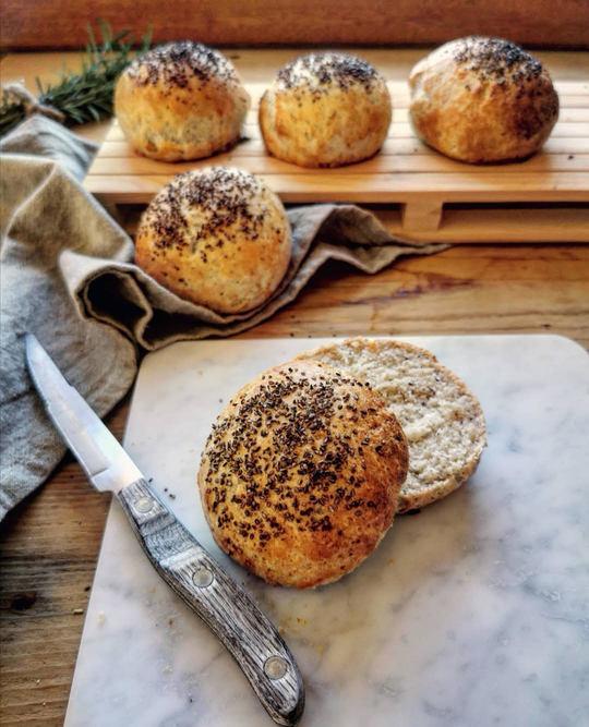 un panino tagliato a metà, su un tagliere di marno, un coltello a lato e sullo sfondo altri panini e un canovaccio