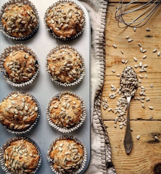 una taglia con muffin vista dall'alto con a lato un cucchiaio di semi di girasole, su un tavolo di legno
