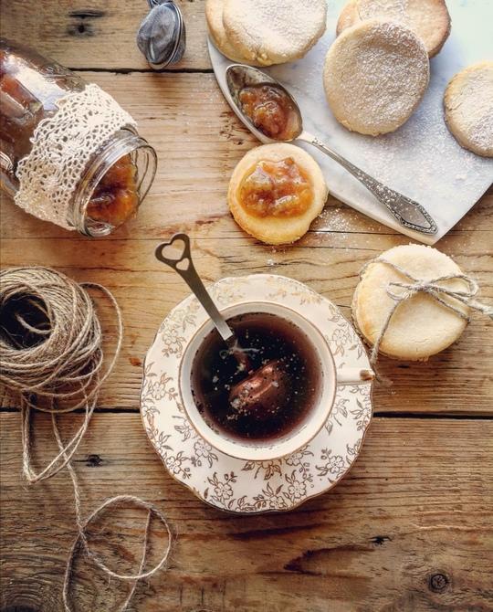 una foto dall'alto con una tazza di the , un gomitolo a lato, un vaso di marmellata rovesciato, e dei biscotti rotondi