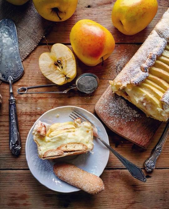 visione dall'alto di una fetta di torta su un piattino con forchetta e biscotto, di lato un plumcale con mele, mele intere gialle e una mezza mela