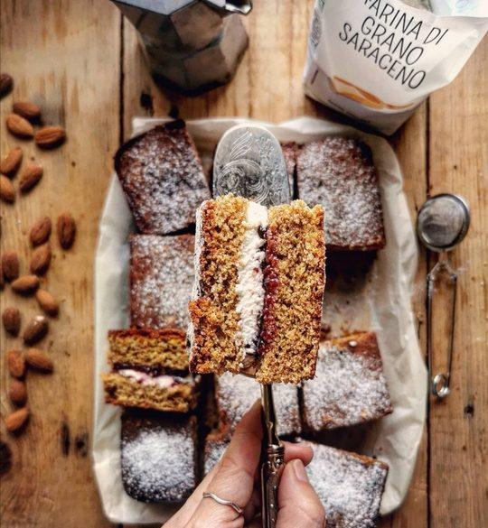 una fetta di torta vista dall'alto e sotto dei quadrati di torra con un sacchetto di farina aperto e delle mandorle sparse sul tavolo
