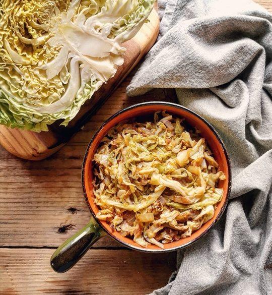 un tavolo visto dall'alto con una padella in coccio con dentro verdura, a lato un canovaccio chiaro e una verza tagliata a metà