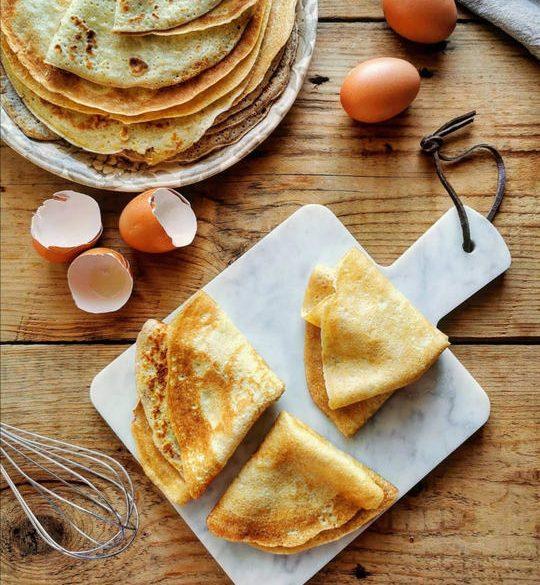 un tagliere bianco visto dall'alto con delle crepes piegate a trinagolo, delle uova rotte sul tavolo e altre intere, vicino ad un piatto con altre crepes rotonde