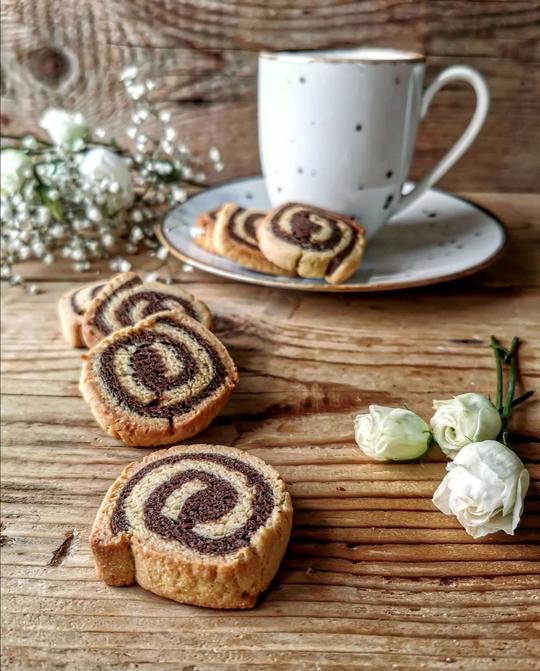 n tavolo di legno con biscotti girella con delle roselline a lato, una tazza mug sullo sfondo