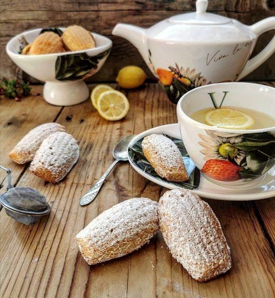 pasticcini a forma di conchiglia su un tavolo di legno, con tazza di the e teiera decorata sul fondo, dei limoni tagliati