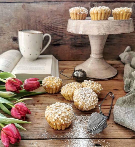 muffin con zuccherini posati su un tavolo con tulipani rossi, sullo sfondo un libro aperto, una tazza e una alzata con altri muffin
