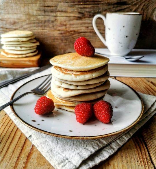 un piatto con pan cake uno sopra l'altro, con dei lamponi, sullo sfondo un libro e una tazza