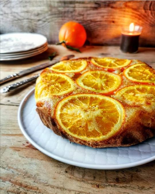 una torta con fette di arancia in superficie, su un tavolo di legno, sullo sfondo una candela e un'arancia