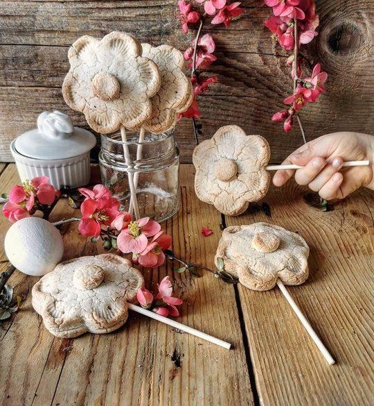 biscotti a fiore con bastoncino e una manina di un bambino che ne ruba uno, sullo sfondo fiori rosa, tutto su sfondo di legno marrone