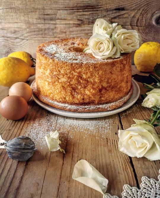 una torta alta a forma di ciambella su un tavolo di legno, con dei limoni e delle rose bianche