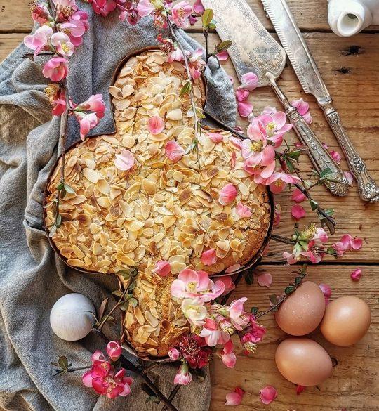 coloma di Pasqua vista dall'alto con delle uova di lato, dei fiori rosa, uno straccio e delle posate vintage