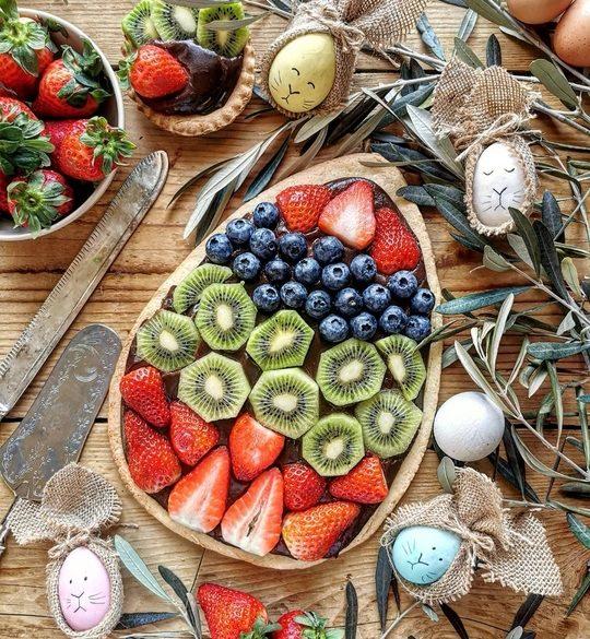 visione dall'alto di una crostata a forma di uovo, con tanta frutta fresca sopra e a lato delle uova colorate decorate, rami di ulivo, un coltello vintage e delle fragole su una ciotola