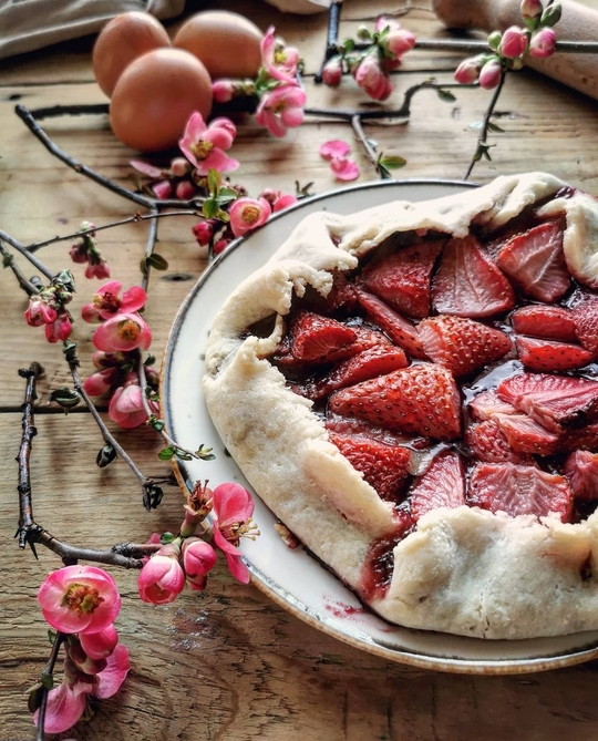 una crostata con fragole, vista da davanti posata su un tavolo di legno con fiori rosa a lato e uova sullo sfondo