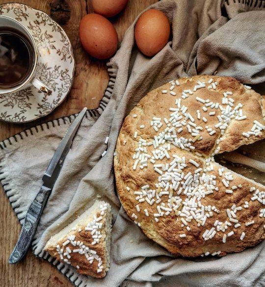 focaccia veneta vista dallìalto, torta rotonda su un canovaccio marrone, con una fetta tagliata a lato, un coltello, una tazza di the e delle uova