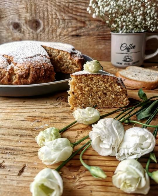una torta semplice tagliata. una fetta in primo piano con delle rose bianche posate su un tavolo, sullo sfondo una tazza con dei fiorellini bianchi