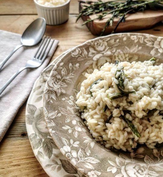 un piatto di risotto con aspargi, sullo sfondo una ciotola con formaggio grattugiato, delle erbe e di lato una forchetta e un cucchiaio