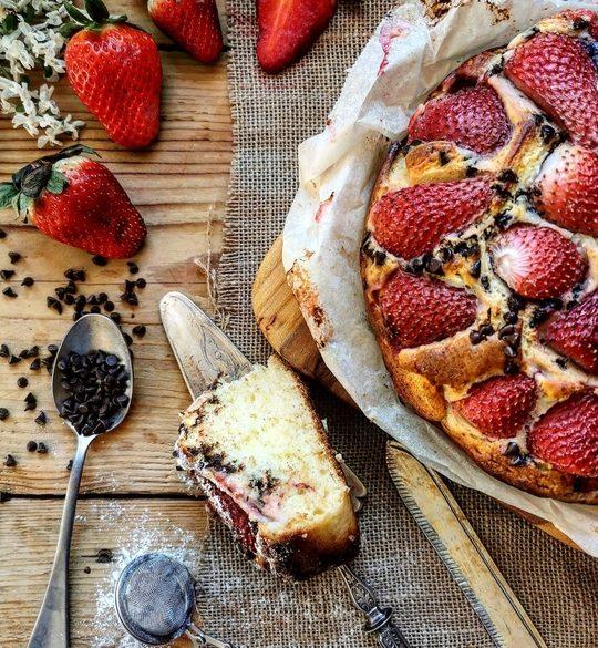 una mezza torta vista dall'alto con fragole e gocce di cioccolato, di lato una fetta tagliata ,un cucchiaio pieno di gocce di cioccolato e delle fragole