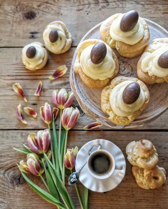 immagine dall'alto di zeppole farcite di crema con ovetti di cioccolato, sul tavolo di legno dei tulipani gialli e arancio e una tazzina di caffè