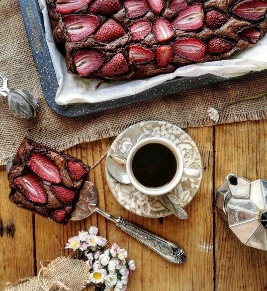 vista dall'alto di una tazza di caffè nero, con un a fetta di torta al cioccolato con le fragole, una moka di caffè e un mazzetto di pratoline a lato
