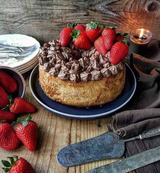 una torta con cioccolato e fragole, su un tavolo, con fragole a lato e una candela accesa