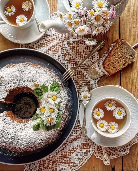 una cimbella vista dall'alto con zucchero a velo, delle margherite a decorazione, a lato una tazza di the con margherite, una teiera e delle margherite