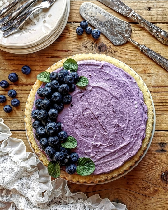 una torta vista dall'alto con crema viola di mirtilli, mirtilli come decorazione e a lato dei piattini