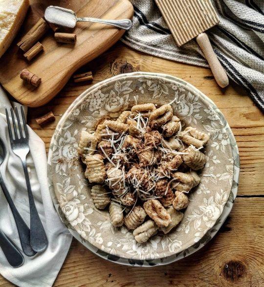vista dall'alto di un tavolo di legno con gnocchi, a lato posate, tagliere con cannella e zucchero