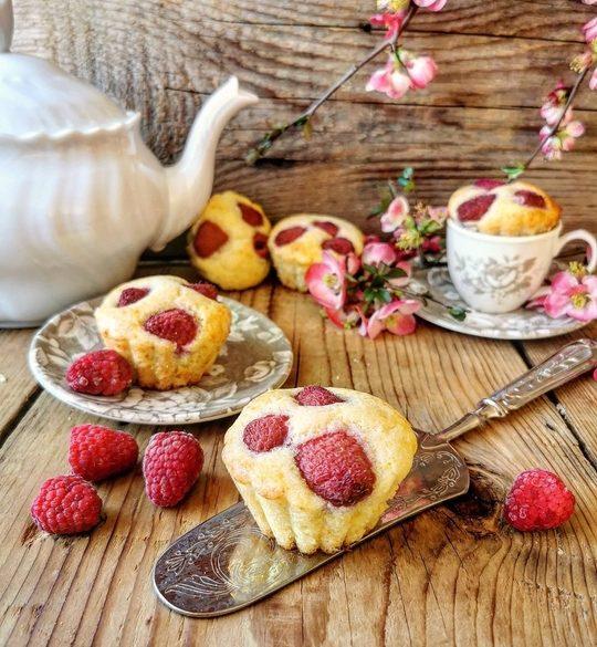muffin ai lamponi visti da davanti su un piano di legno, con nello sfondo una teiera bianca