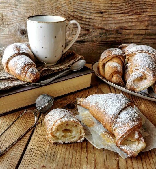 piano di legno e cornetti brioches zuccherate, una tazza mug sopra un libro chiuso