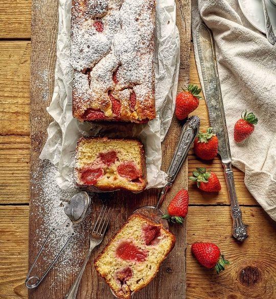 plumcake tagliato visto dall'alto con fragole a lato uno straccio e un coltello lungo