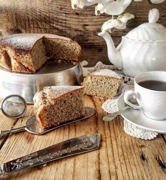 una torta su un tavolo di legno con una fetta tagliata, una tazza a lato e una teiera bianca sullo sfondo