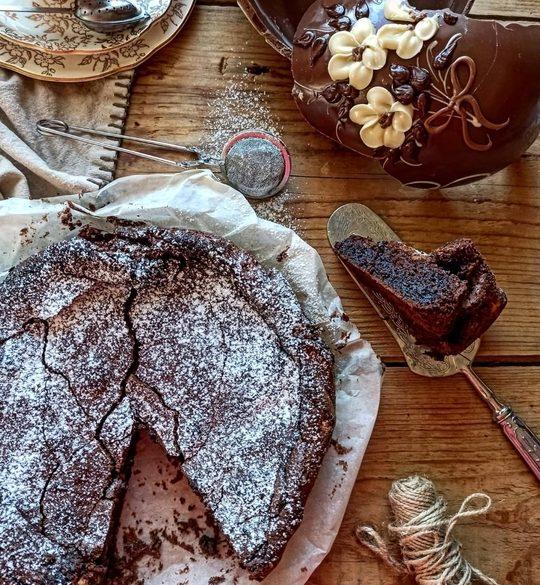 una torta al cioccolato vista dall'alto, cosparsa da zucchero a velo, con una fetta tagliata a lato e un uovo di Pasqua rotto vicino