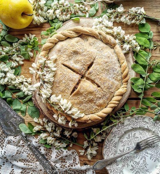 una apple pie vista dall'alto con fiori di acacia intorno, una mela gialla, un piattino con una forchettina