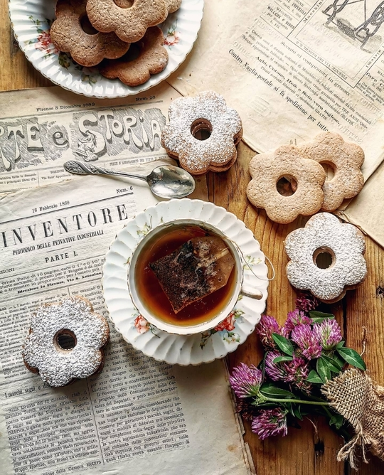 vista dall'alto di una tazza vintage di the, dei biscotti a fiore con zucchero a velo, posati su fogli di giornale e un mazzolino di fiori di campo rosa
