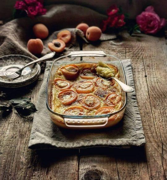 una teglia con un dolce di albicocche, sopra uno straccio e un tavolo di legno, sullo sfondo delle albicocche e delle rose, dei piattini e una forchetta