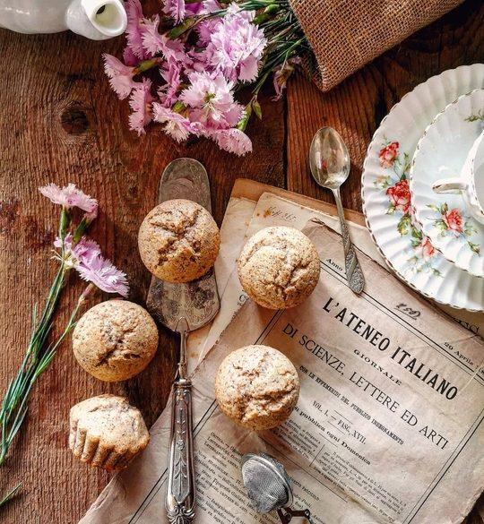 dolcetti muffin visti dall'alto posati su vecchi fogli di giornale, a lato una tazzina vintage e dei fiori rosa