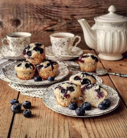 muffin ai mirtilli su un piano di legno, posati su due piattini, sullo sfondo una teiera e due tazze di the