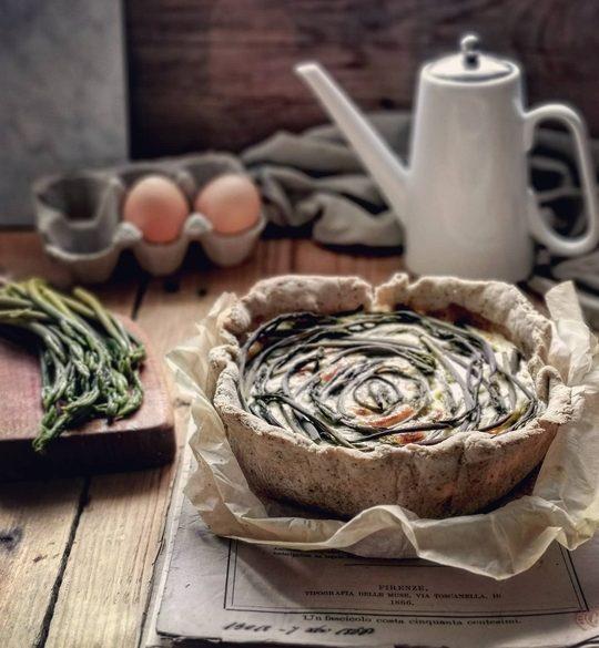 una torta salata con delle erbe, posata su un piano di legno e dei fogli, a lato dei germogli su un tagliere, sullo sfondo una oliera, uno straccio e due uova
