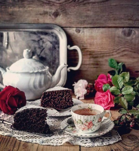 un contesto vintage con una tazza di thè antica, con fiorellini , a lato due fette di torta al cacao, delle rose rosse e rosa posate e una teiera sullo sfondo con un vassoio di argento