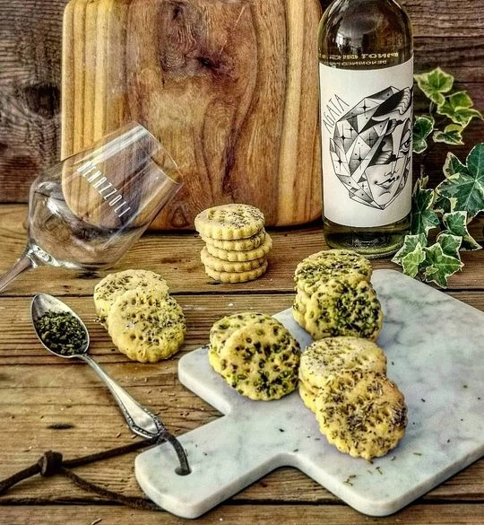 un tagliare bianco in marmo con sopra biscotti salati e sullo sfondo una bottiglia di vino con un bicchiere a lato