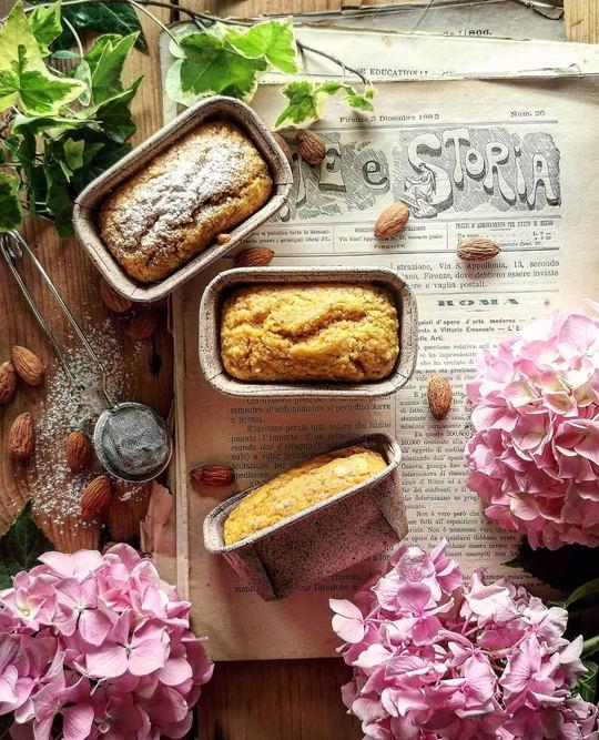 vista dall'alto di piccoli plumcake alle carote, posati su fogli di giornale, dei fiori rosa a lato .
