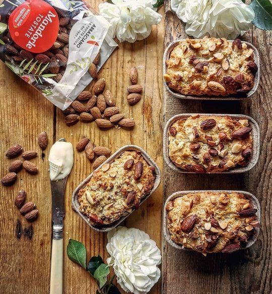 mini plumcake visti dall alto, con delle rose bianche e un coltello pieno di formaggio da spalmare, un sacchettino di mandorle a lato.