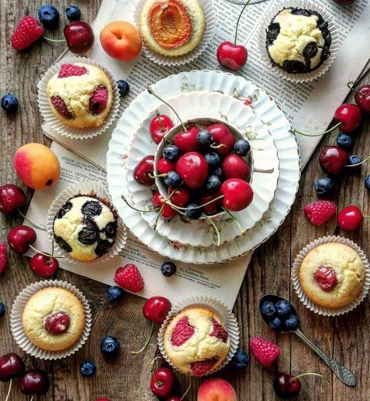 una tazza piena di frutta vista dall'alto con dei muffin intorno, con frutta