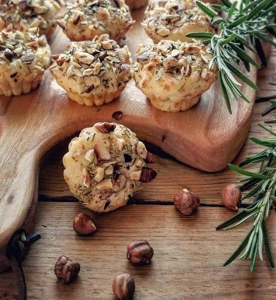 muffin posati su un tagliere in primo piano, con un rametto di rosmarino a lato